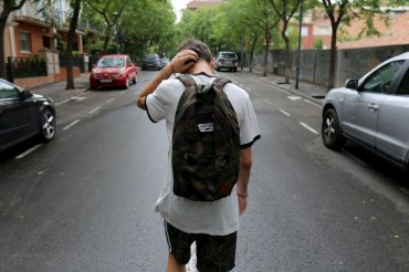 Teenage boy walking in the middle of an empty street during the day. It has just rained, and he is scratching the back of his neck as he walks, deep in thought.