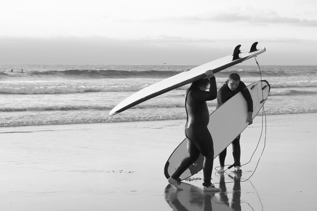 Teen Boys Carrying Surf Boards On Beach - Teen Rehab
