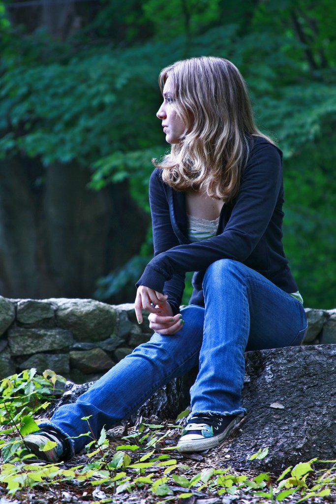Teenage Girl Sitting On Rock Looking Away - Teen Rehab