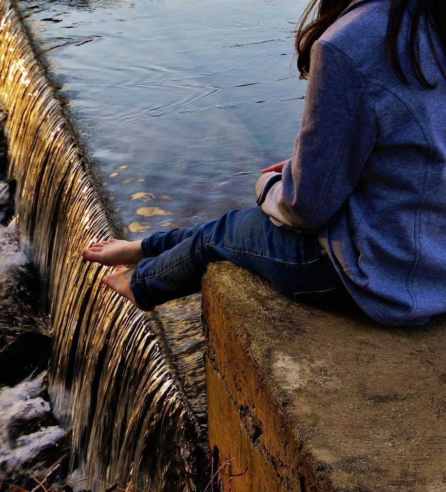 Teenage Girl Sitting On Stone Wall By Water - Teen Rehab