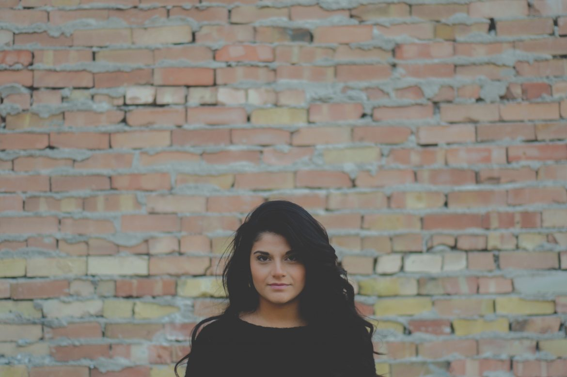 girl woman curly hair brick wall portrait person