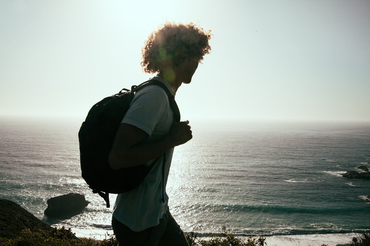 young-man-hiking-by-ocean