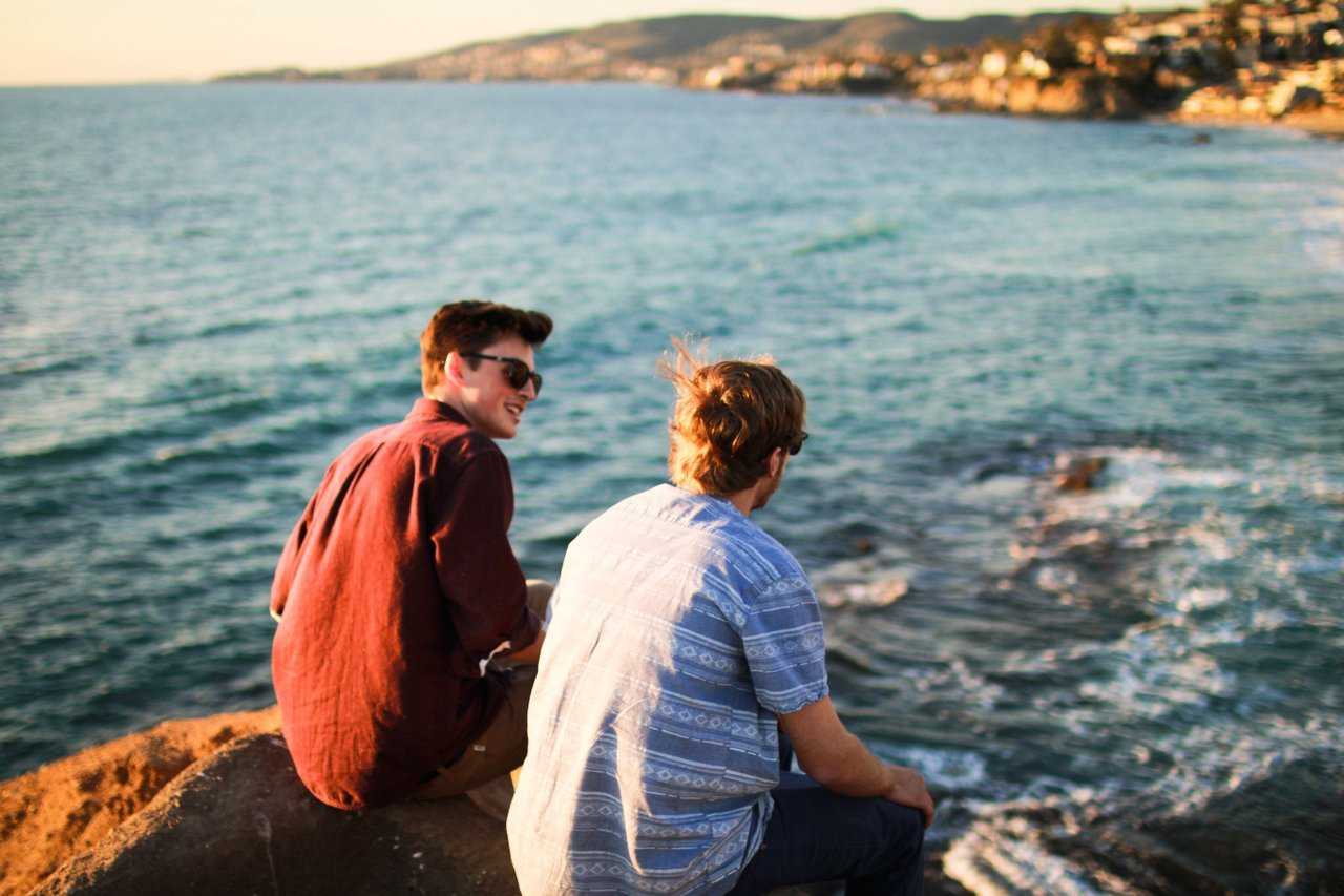 guys-sitting-by-ocean-talking