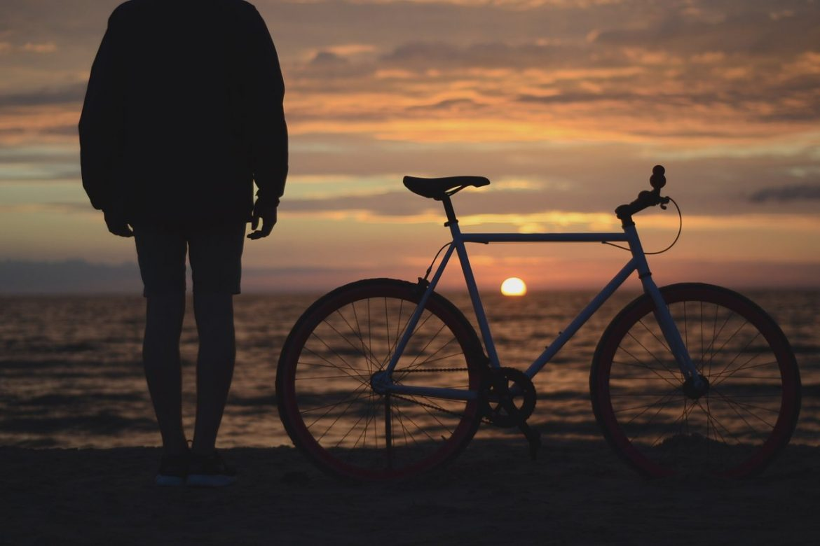 man bicycle beach ocean sunset