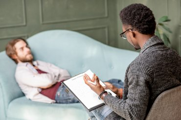 A therapist speaks to a patient with a clipboard in his hand. The male patient lays on a couch with his arms folded, staring at the wall.