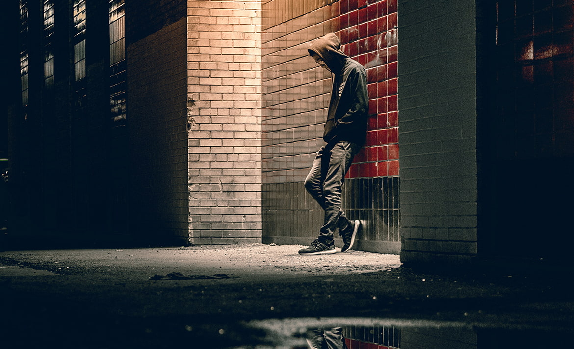 Young man leans against a lit wall at night.