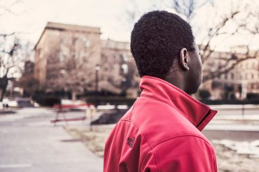 Young man faces away on a cool day, looking into the distance.