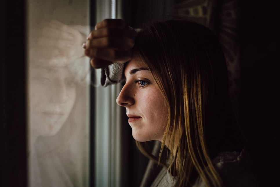 Young woman resting head against the back of her hand, leaning against a window and looking out it.