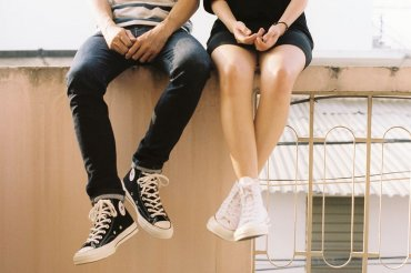 A young man and woman sitting on a railing. Their hands look like they're having a deep conversation.