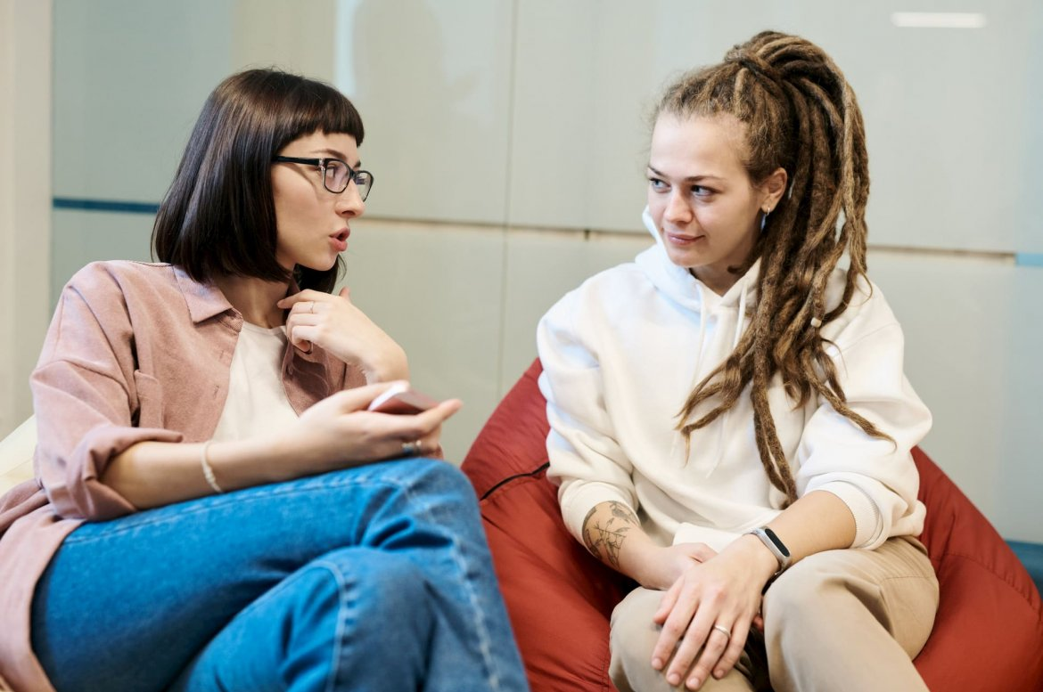 Two young women sit beside each other on a set of beanbag chairs in conversation. One woman seems a bit older, and might be mentoring or counseling the younger.