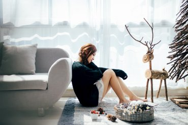 A young woman sits beside a couch among Christmas decorations, looking contemplative and nearly sad.