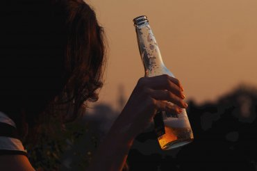 Young woman holding a beer bottle at sunset.