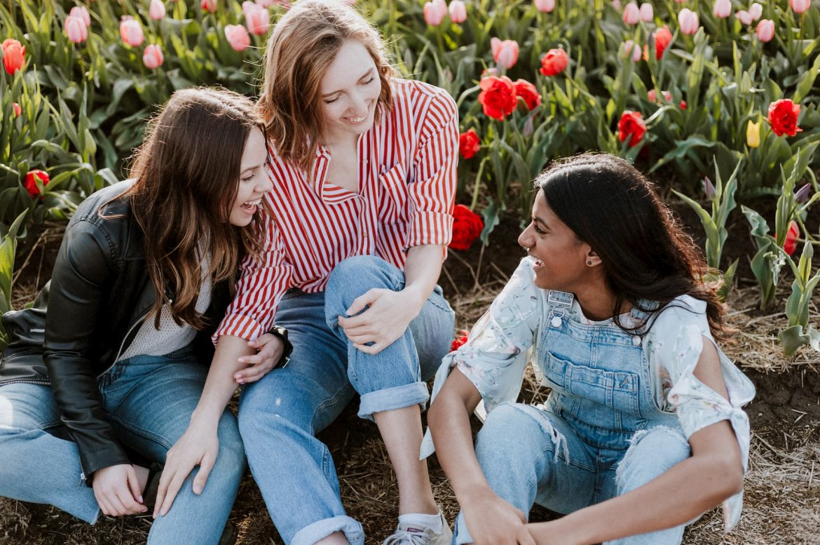 Three young women sit among flowers. They're laughing and enjoying each other's company.