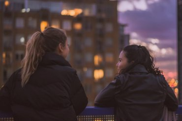 Two young women lean on a railing on an urban balcony during sunset, looking over at one another.