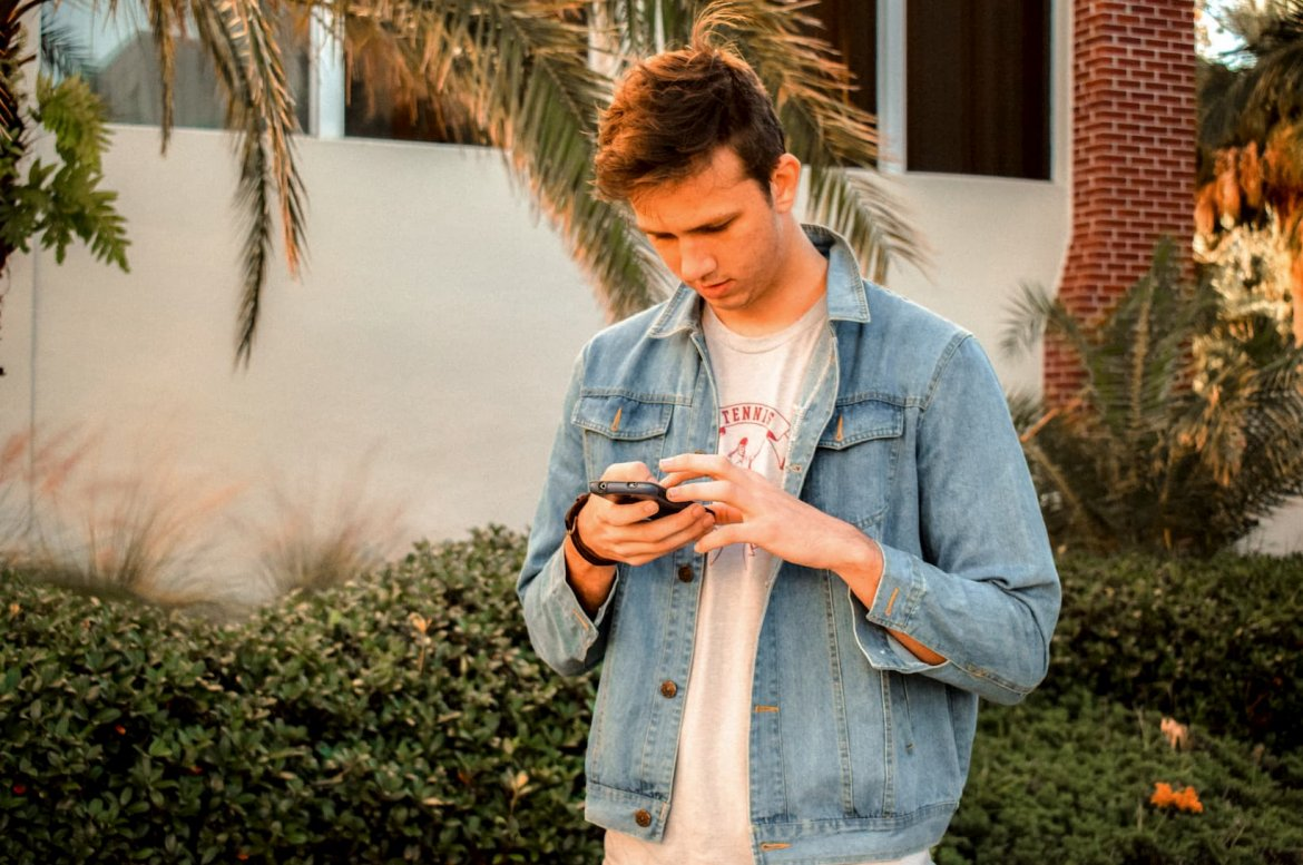 a young man wearing a denim jacket reading something on his phone.