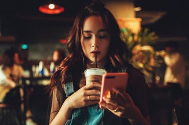 A teen girl is engrossed by her phone as she drinks in a coffee shop.